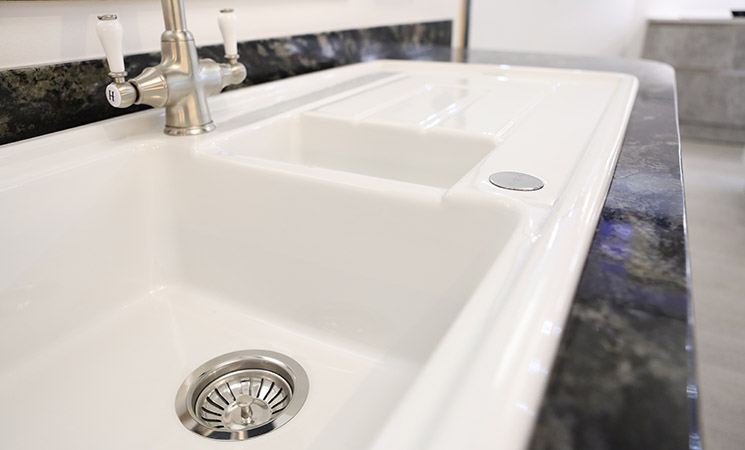 White ceramic sink in a country style fitted kitchen
