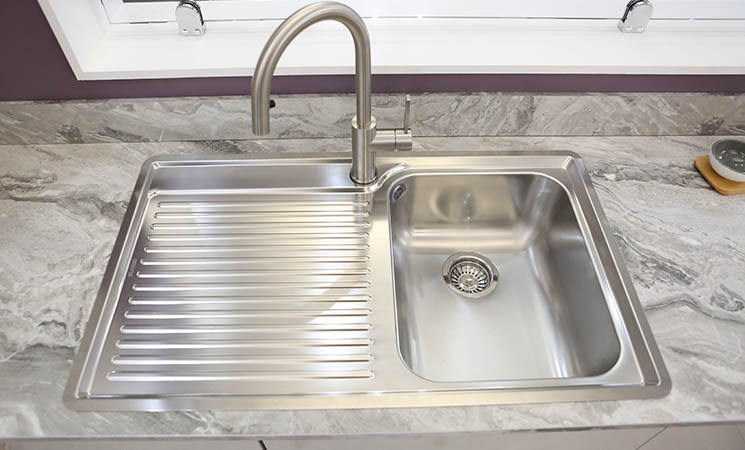 Stainless steel sink set in a grey marble worktop