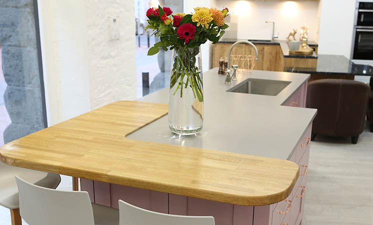 Wooden worktop with pink fitted kitchen cabinets
