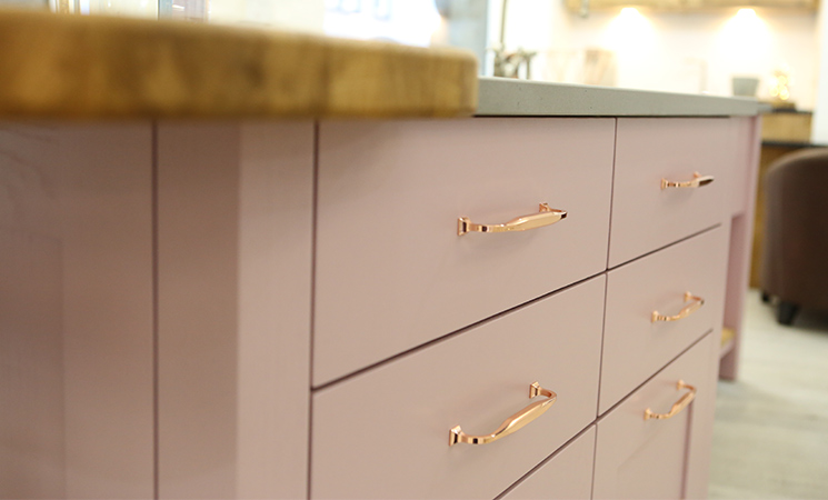 Copper bar handles on a modern pink kitchen cabinet