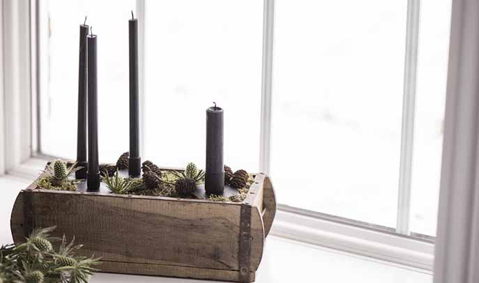 Tall black candles in a wooden box contrast against the scandi white backdrop