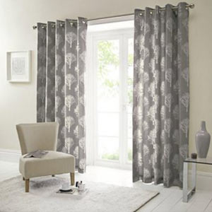 Patterned curtains hanging in front of a large window
