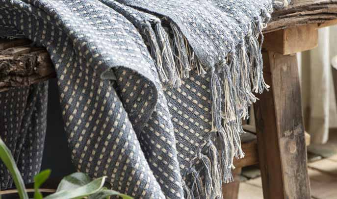 Scandi grey neutral throws on a natural wood bench