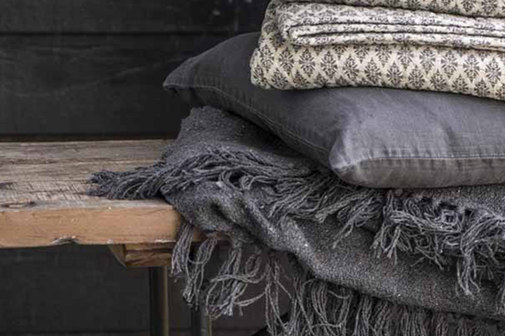 Scandi-Nordic textured grey blankets and throws on natural wood bench