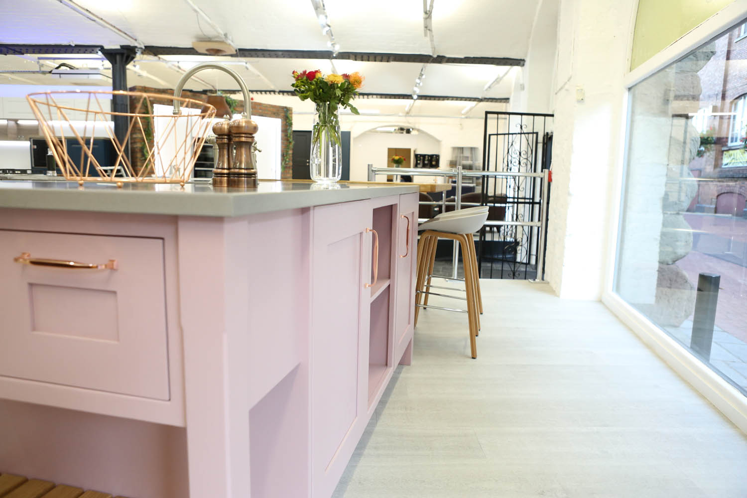 Pink fitted kitchen with copper handles