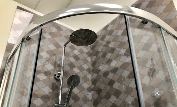 shower head in enclosure with tiles