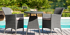 A 2 seat garden furniture set in front of a pool