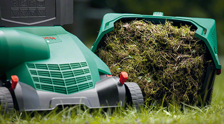 A close up of a Bosch mower and collection of grass