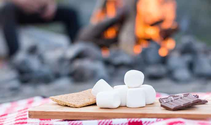 Traditional smores ready to eat next to a warm glowing fire